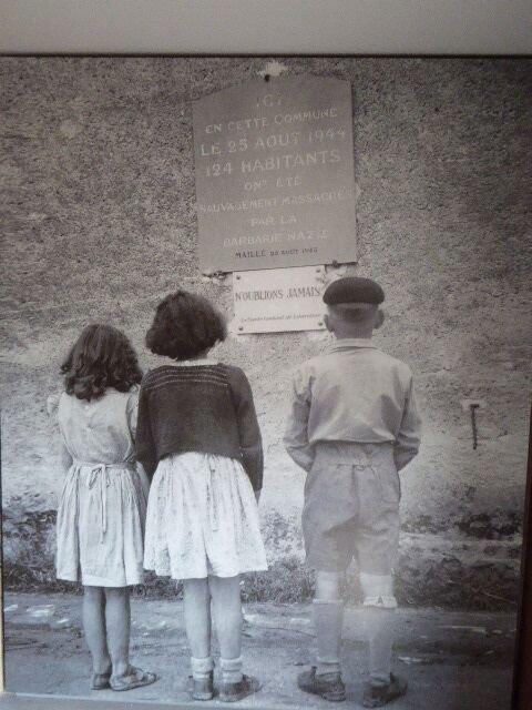 Drei Kinder vor der Gedenktafel am Rathaus (© Maison du Souvenir)